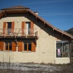 Maison en monomur avec couverture en tuile de terre cuite plates. Balcon traditionnel en mélèze